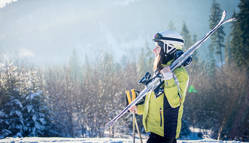 Young Woman with Ski Equipment in Mountains