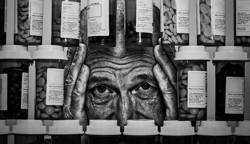 Man behind bottles of Analgesic Opioids