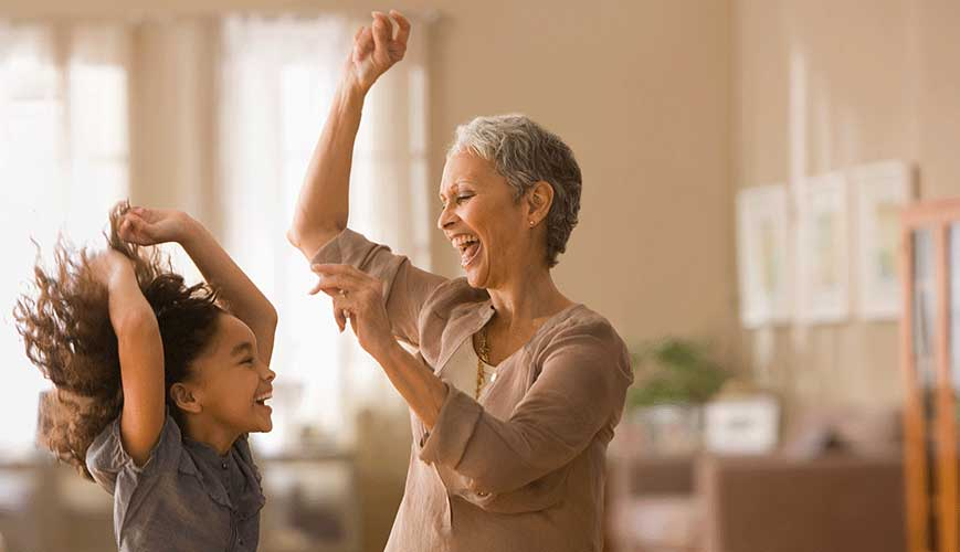 Grandma and grandchild dancing in livingroom