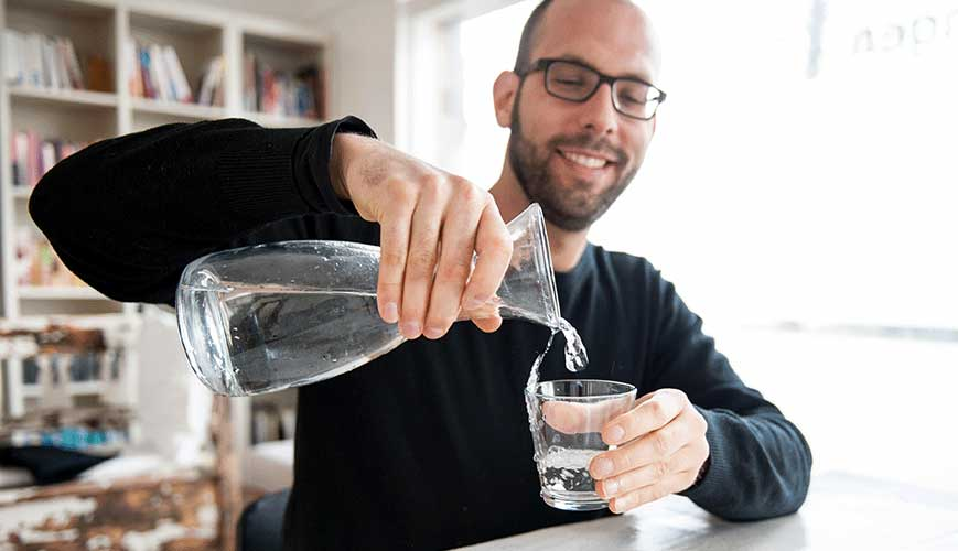 Man Pouring Glass of Water from Craft