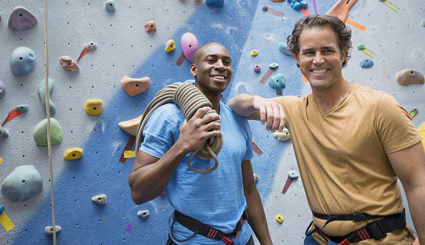 Male Friends Rock Climbing in Gym
