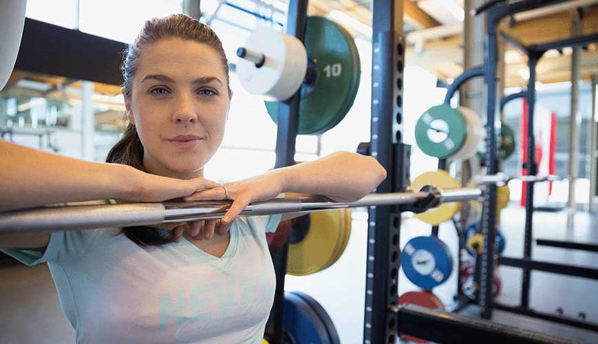 Portrait Confident Woman at Barbell in Gym