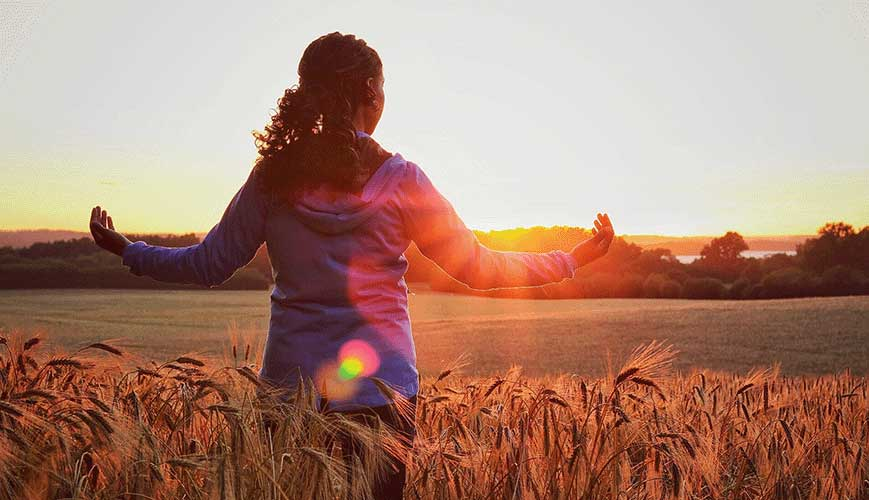 Woman holing our her arms in field