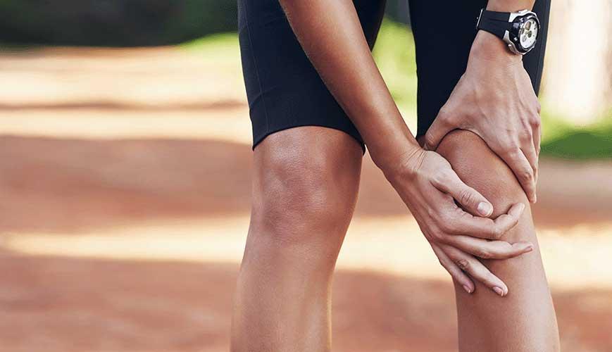 Woman Runner Holding Knee in Pain