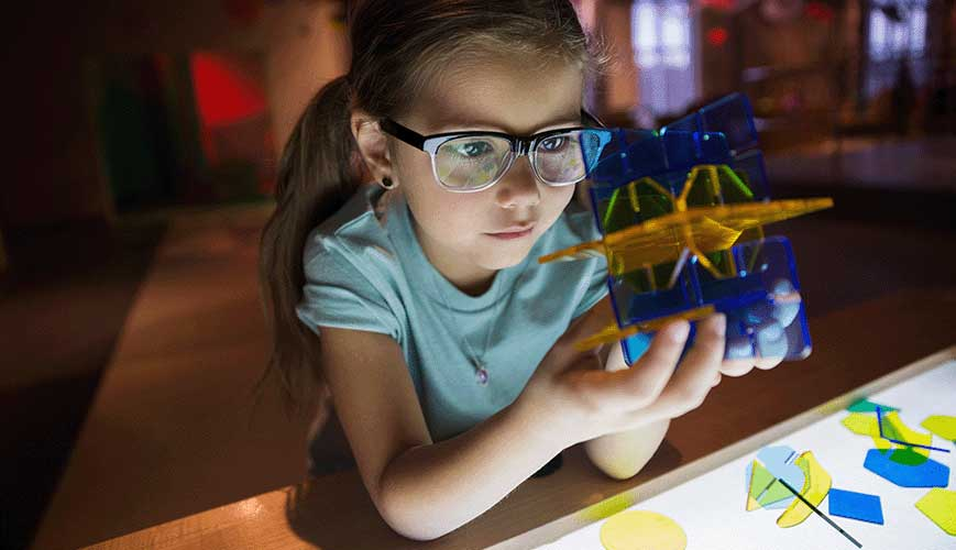 Curious Girl Holding Geometric Shape in Science Center