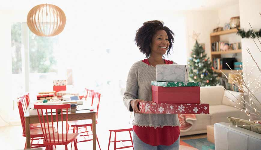 Woman Standing with Wrapped Holiday Gifts
